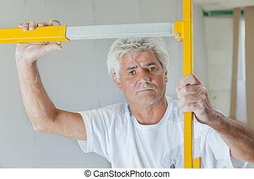 Builder holding a metal frame