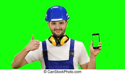 Builder holds a phone in his hands and shows a thumbs up....