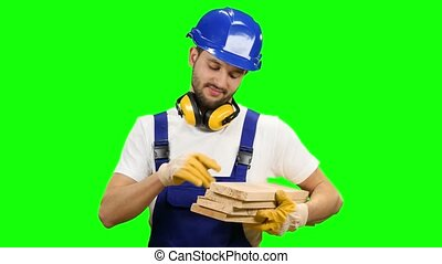Builder holds the wooden boards in his hands and smiles. Green screen