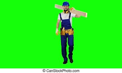 Builder in a helmet goes to work with wooden boards in his hands. Green screen