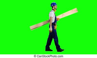 Builder in a helmet goes to work with wooden boards in his hands. Green screen. Side view
