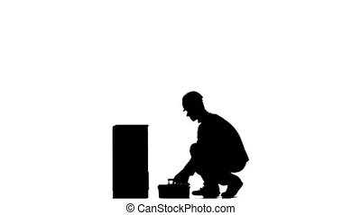 Builder in a helmet hammers a nail with a hammer. Silhouette. White background