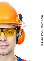 builder in hard hat, earmuffs and goggles - close-up...