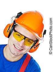 builder in hard hat, earmuffs and goggles
