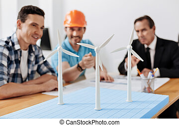 Builder in hard hat pointing at the wind turbine sail