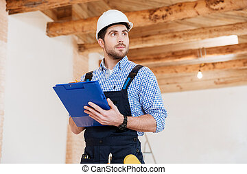 Builder in hardhat with clipboard and pencil indoors