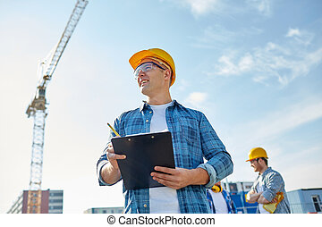 builder in hardhat with clipboard at construction
