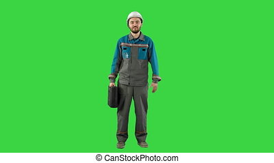Builder in helmet with a suitcase says on camera on a Green Screen, Chroma Key.