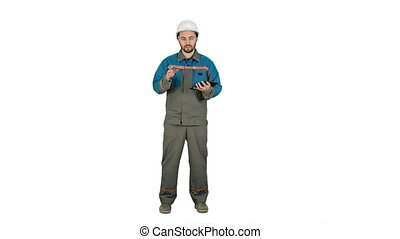 Builder in helmet work with tablet computer, talk on camera on white background.