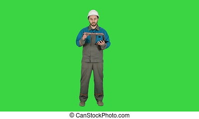 Builder in helmet work with tablet computer, talk on camera on a Green Screen, Chroma Key.