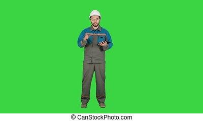 Builder in helmet work with tablet computer, talk on camera...