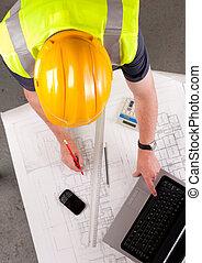 Builder inspects construction plans.