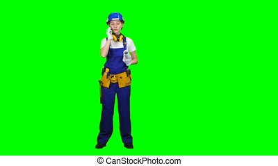 Builder is standing and talking on the phone with a drawing in her hands. Green screen