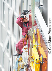 builder joiner installing glass window on building