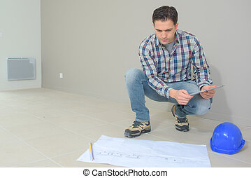 Builder kneeling down by plans