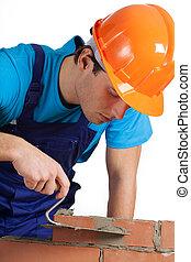 Builder layering bricks - A closeup of a builder in orange ...