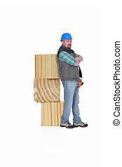 Builder leaning against blocks of wood