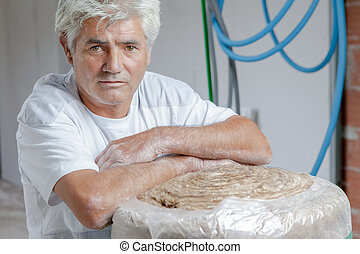 Builder leaning on roll of insulating material