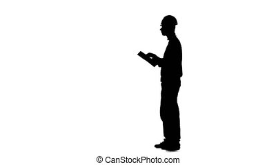Builder looks at the paper plan of the building. Silhouette....