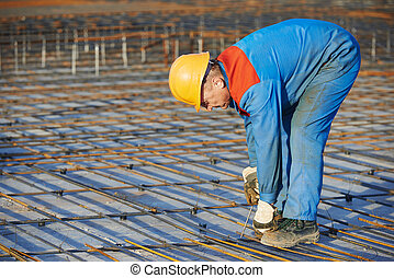Builder making reinforcement for concrete