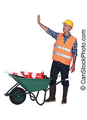 Builder making stop gesture whilst stood with traffic cones