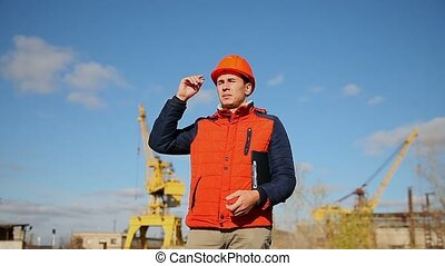 builder man in a helmet corrects orange shouts calling shout against the blue sky and a crane