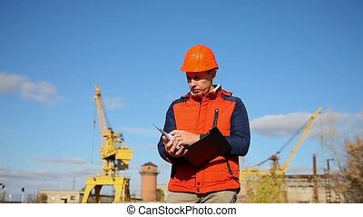 builder man in helmet shows a finger away orange against the blue sky and a crane