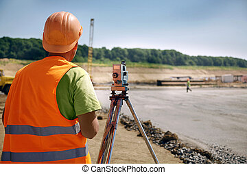 Builder on a building place - Builder in orange helmet and...