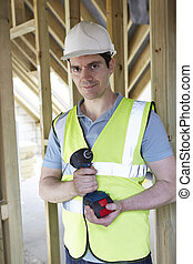 Builder On Construction Site Holding Cordless Drill