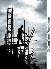 builder on scaffold building site - silhouette of...