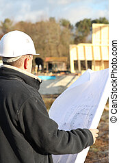 Builder on site with plans