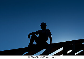 Builder or carpenter resting on top of roof structure -...