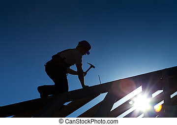 Builder or carpenter working on the roof - silhouette with strong back light