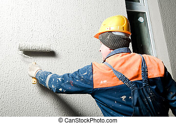 facade worker at decoration plastering works outside building wall with roller