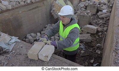 Builder put bricks on the edge of pit