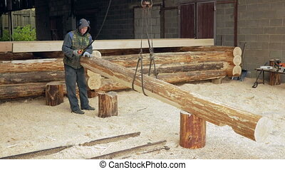Builder raises wooden timber with Overhead Winch Crane. A man holds a log and transfer it to the future home