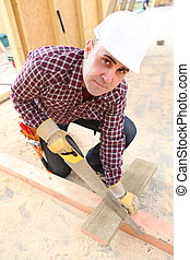 Builder sawing wood