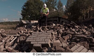 Builder sits on the bricks of ruins