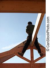 Builder sitting on a beam