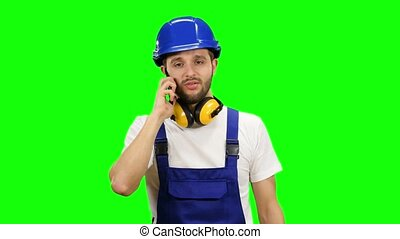Builder speaks on the phone with his boss. Green screen