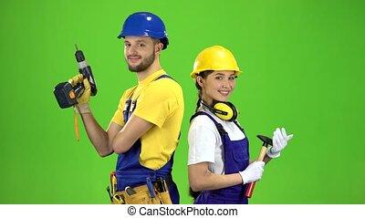 Builder standing a guy holding a drill, a girl hammer. Green screen