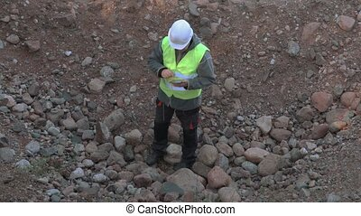 Builder standing in the pit and using tablet