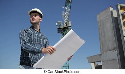 Builder stands with set of plan at the bulding under construction