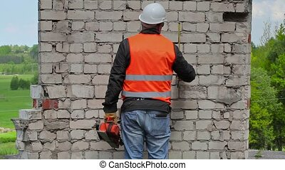 Builder take measurements on the brick wall