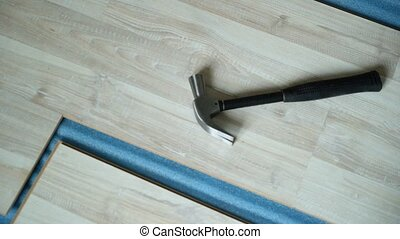 Builder takes a hammer. Repair of the apartment, laying laminate flooring. Construction