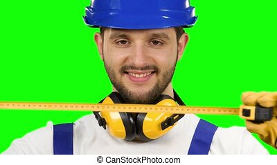 Builder takes measurements with the help of a tape measure. Green screen. Close up