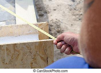 Builder taking a measurement