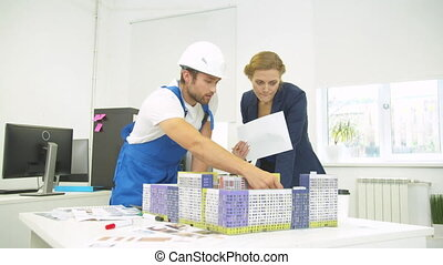 Builder talk to woman with sheme in hand, they discuss project of houses