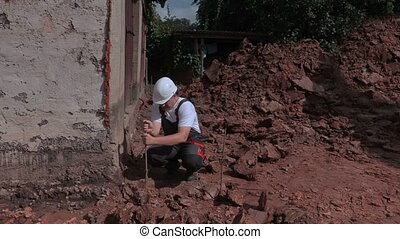Builder talking and fixing ground level