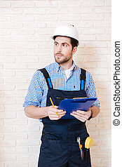 Builder thinking about something and holding a clipboard